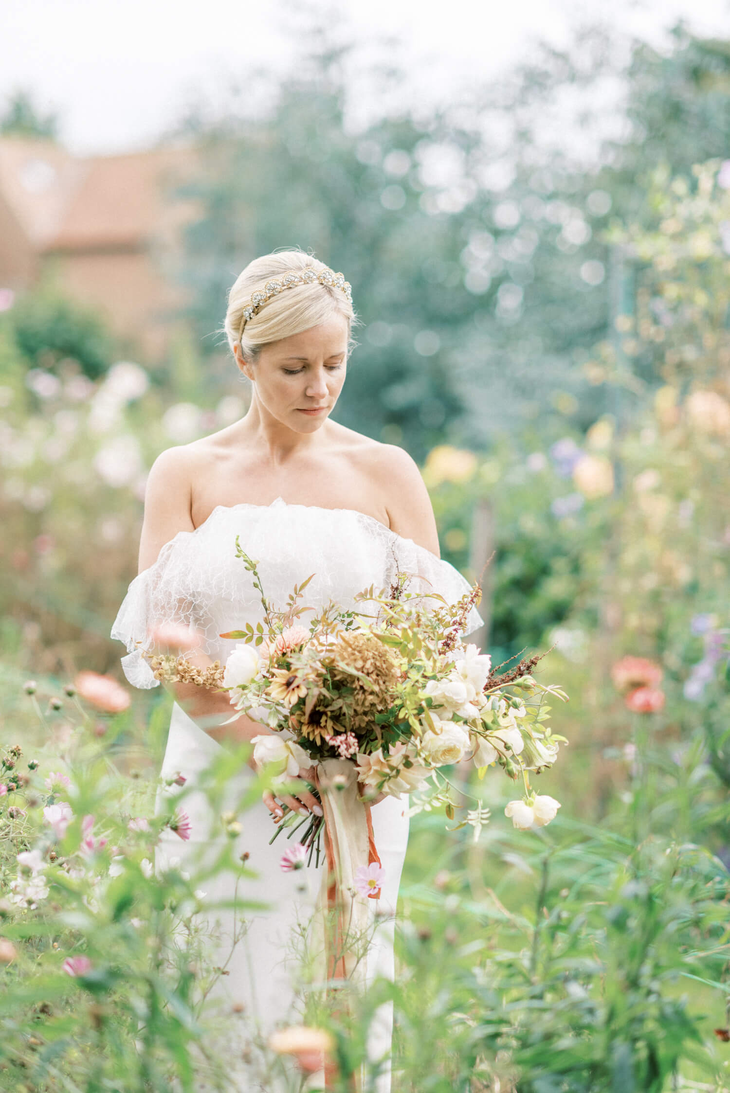 English Countryside Autumn Wedding at a Flower Farm | Photos and Text by Cristina Ilao Photography | In photo: simple bride walking in the middle of a flower farm and wearing an elegant wedding dress by UK dress designer Cherry Williams London
