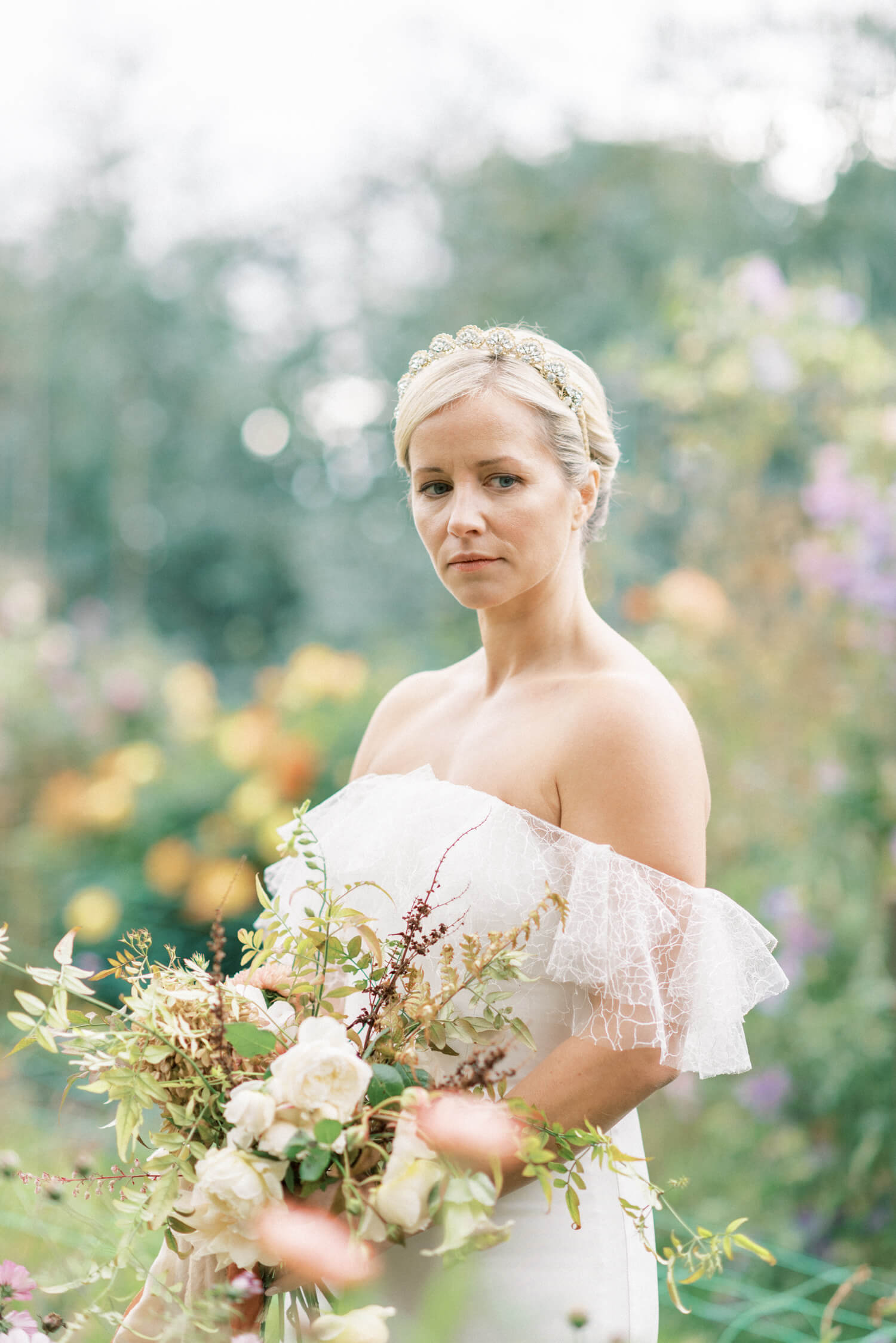 English Countryside Autumn Wedding at a Flower Farm | Photos and Text by Cristina Ilao Photography | bride portrait in the middle of Holme Flower Farm. Bride is wearing a white lace off shoulder wedding dress while holding an autumn wedding bouquet