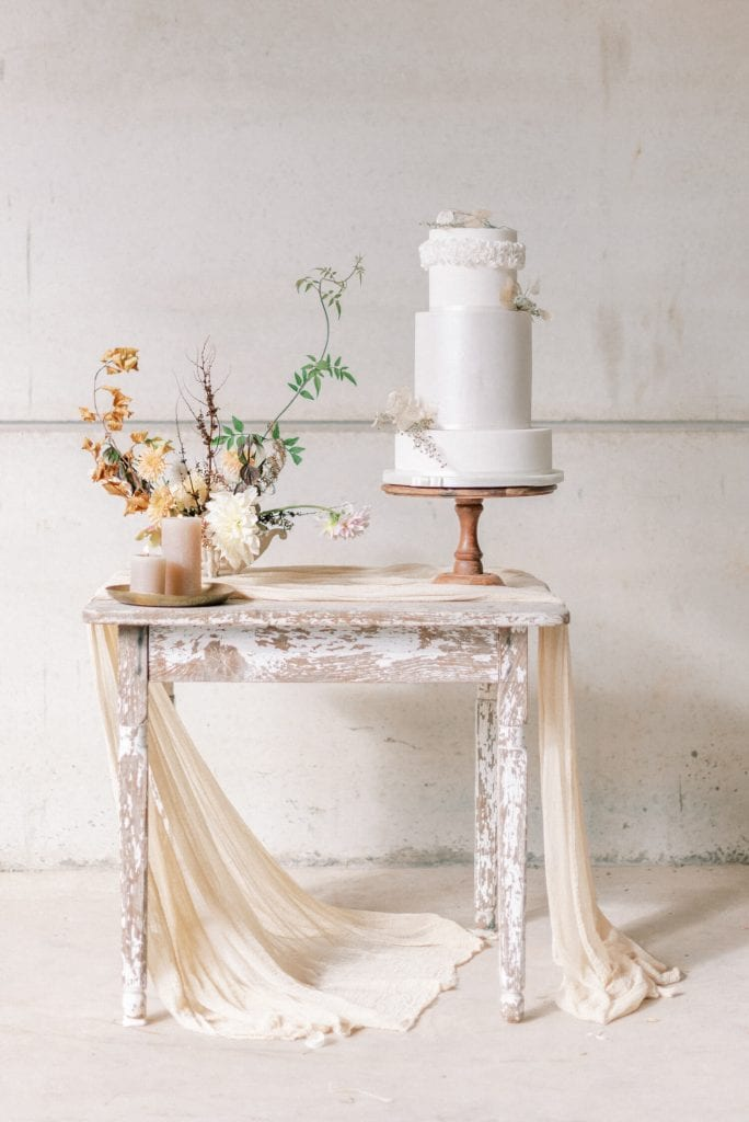 English Countryside Autumn Wedding at a Flower Farm | Photos and Text by Cristina Ilao Photography | In Photo antique shabby chic table with beige silk table runner and three tier minimalist white wedding cake by Poppy Pickering Cakes