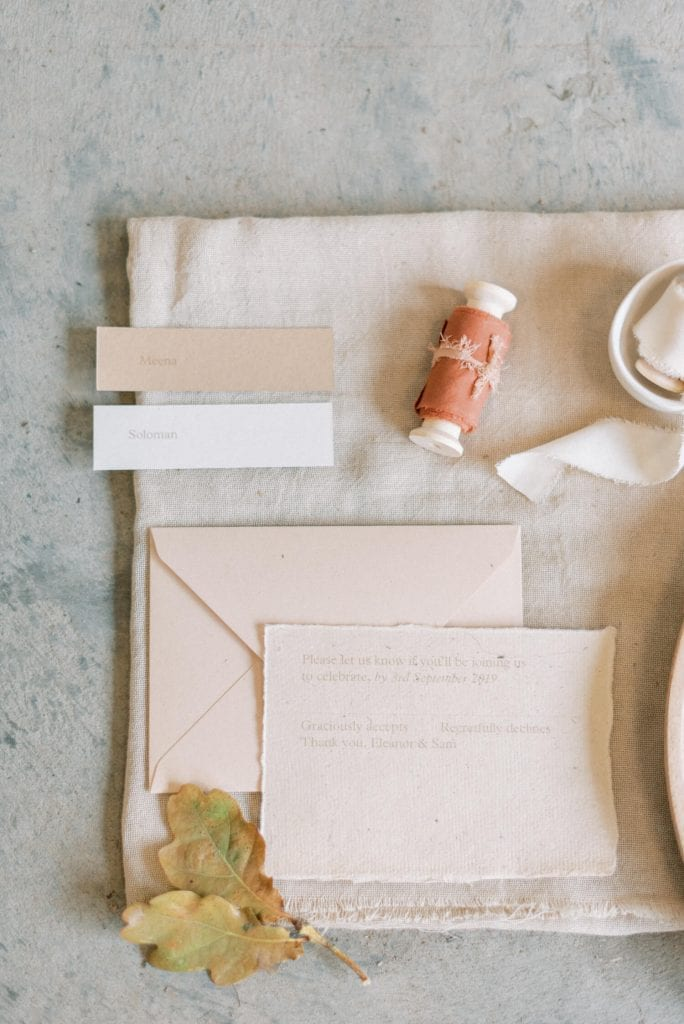 wedding stationery suite using handmade paper designed by Bureau Design. Flatlay photo styled with nude and cream neutral colour palette using silk table runner, autumn dried foliage and silk ribbons