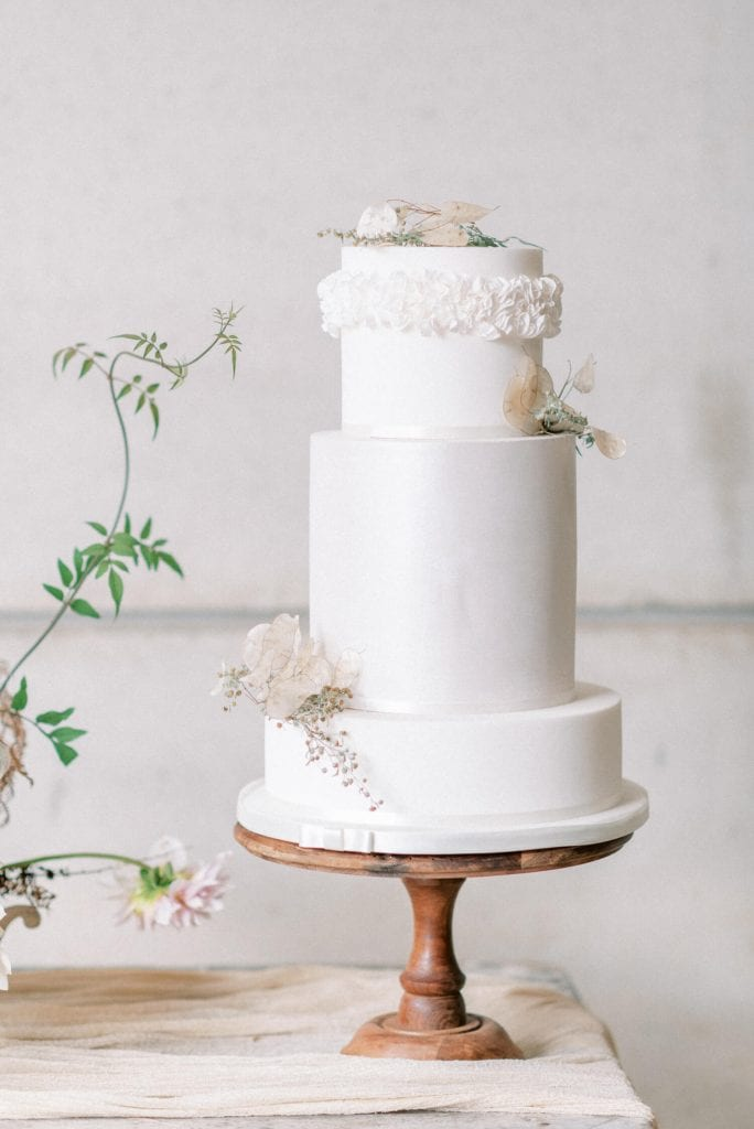 English Countryside Autumn Wedding at a Flower Farm | Photos and Text by Cristina Ilao Photography | In photo: three layer simple white wedding cake with ruffled sugar icing and dried flowers by Poppy Pickering Cakes