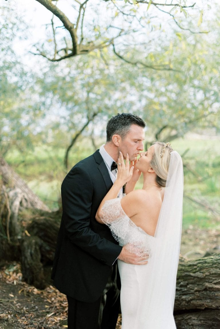 English Countryside Autumn Wedding at a Flower Farm | Photos and Text by Cristina Ilao Photography | In photo: bride and groom romantic kiss under the olive trees. Bride is wearing a CHerry Williams London off shoulder mermaid cut wedding dress and groom is wearing a black tuxedo