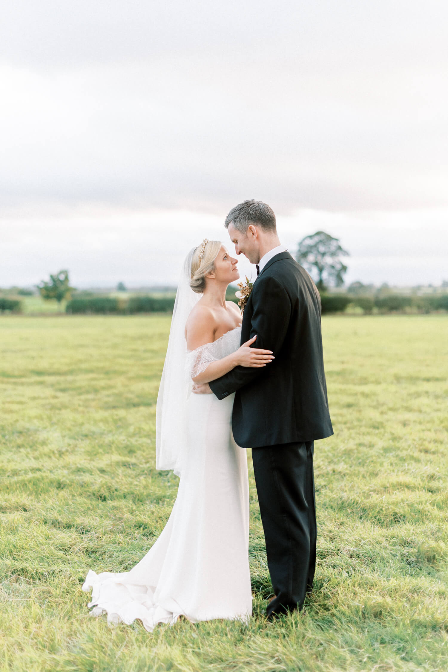 UK destination wedding in a Yorkshire flower farm | In photo: full body portrait of bride and groom looking at each other romantically. Bride is wearing a custom fitted off-shoulder white wedding dress by Cherry Williams London and accessories by Agnes Hart. Groom is wearing a black wedding suit