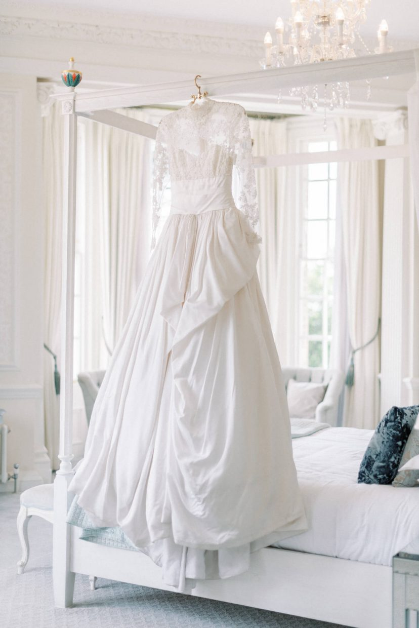White Marchesa wedding gown with lace top longsleeves in chantilly lace; silk brocade ball gown full skirt; hedsor house light bright and airy bridal suite with canopy bed in white wooden style with accent; white nautral plain wedding preparation room with luxury glass chandelier | Photo by London and Newcastle UK based light bright and airy Filipina wedding photographer Cristina Ilao