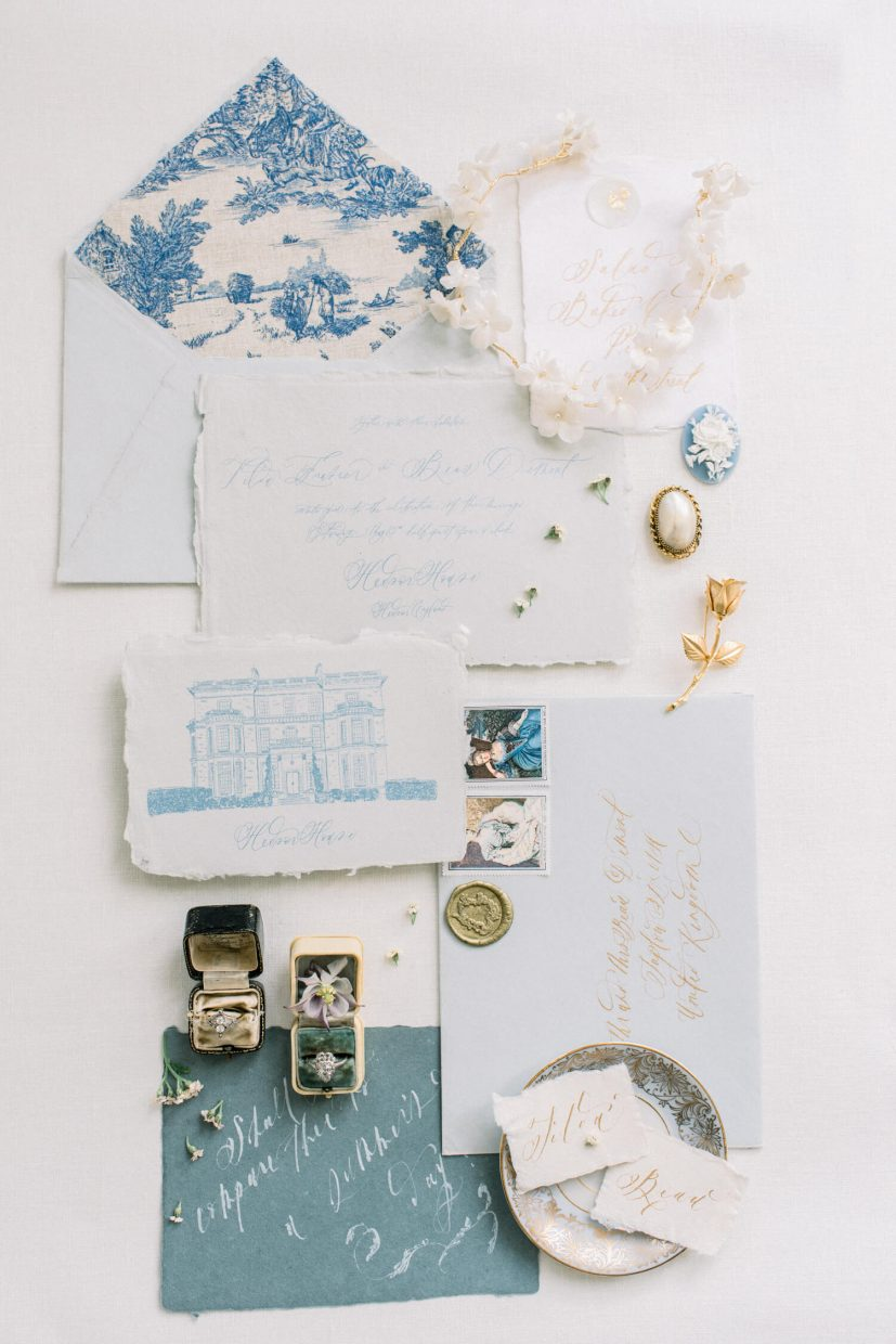 hedsor house stationery suite with calligraphy in blue and gold ink; hedsor house venue illustration; vintage antique ring wedding boxes; handmade paper and calligraphy; cameo rose; gold bridal accessories; engagement ring vintage ; toile envelope liner; white clay polymer bridal hair accessories; plain white styling background | Photo by London and Newcastle UK based light bright and airy Filipina wedding photographer Cristina Ilao