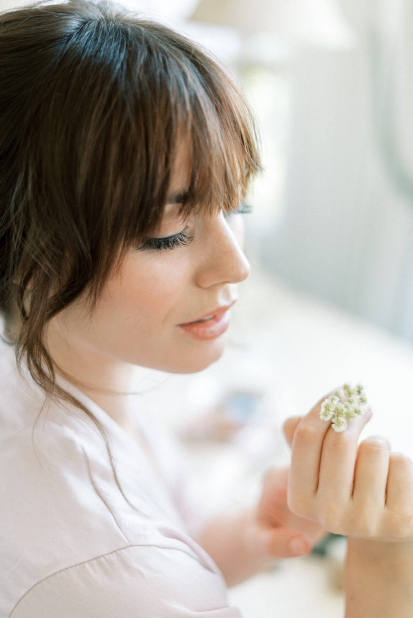 best bridal make-up and hairstyle; fringe bangs and updo; no make-up natural neutral palette young fresh look; brunette bride smelling small tiny flowers | Photo by London and Newcastle UK based light bright and airy Filipina wedding photographer Cristina Ilao