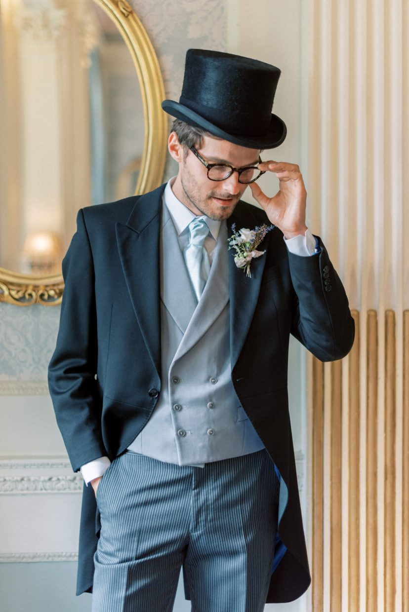 hedsor house spring summer wedding; black groom top hat; armani long coat with pale blue vest and neck tie pin stripe trousers | Photo by London and Newcastle UK based light bright and airy Filipina wedding photographer Cristina Ilao