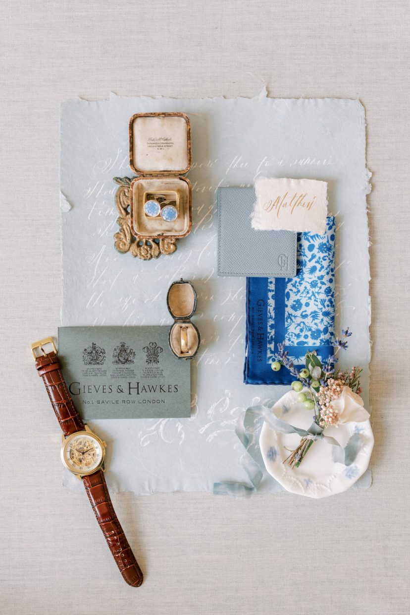 groom accessories styled on a flatlay; gieves and hawkes leather strap brown and gold watch; vintage ring box and bulgari groom gold matte wedding ring; pale blue cuff links; leather wallet; calligraphy white font on pale blue handmade paper | Photo by London and Newcastle UK based light bright and airy Filipina wedding photographer Cristina Ilao