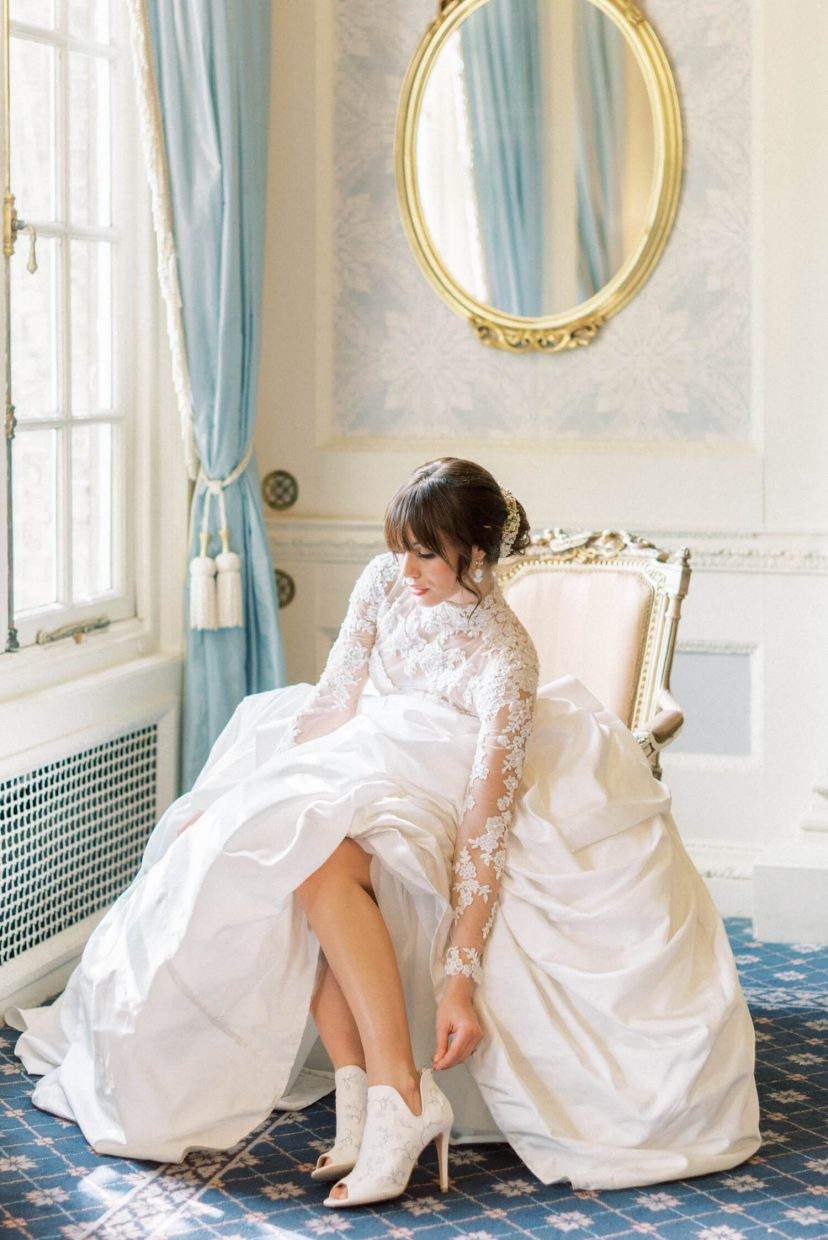 hedsor house spring summer wedding; bridal portrait by the big window and pale blue vintage floor to ceiling heavy drapes; vintage mirror with gold details; pale blue wallpaper; white wall panel | Photo by London and Newcastle UK based light bright and airy Filipina wedding photographer Cristina Ilao