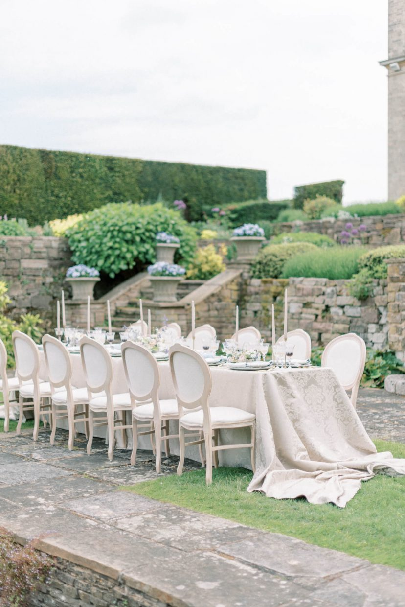 hedsor house spring summer garden wedding reception table with luxury fabric table cloth brocade pattern; french louis guest chairs; erik and ester taper candles on vintage candlesticks; garden flower urns in the background | Photo by London and Newcastle UK based light bright and airy Filipina wedding photographer Cristina Ilao