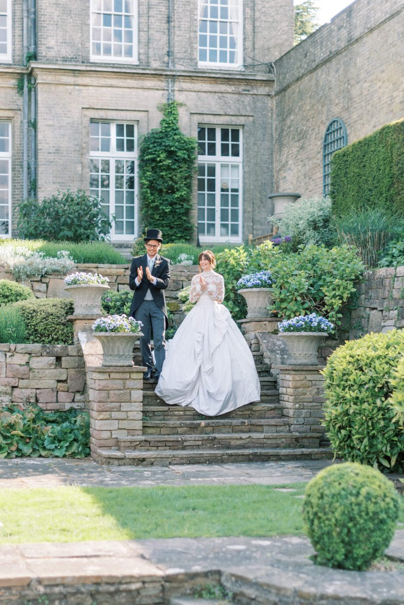 hedsor house spring summer wedding inspiration with bride and groom heading to reception and laughing while going down the garden stairs; georgian architecture in the background | Photo by London and Newcastle UK based light bright and airy Filipina wedding photographer Cristina Ilao