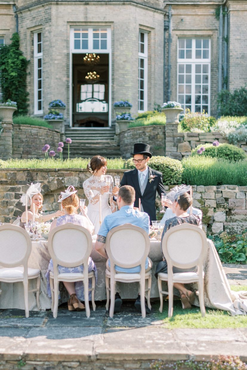 hedsor house sping summer wedding inspiration garden reception with bride and groom toasting with the guests | Photo by London and Newcastle UK based light bright and airy Filipina wedding photographer Cristina Ilao