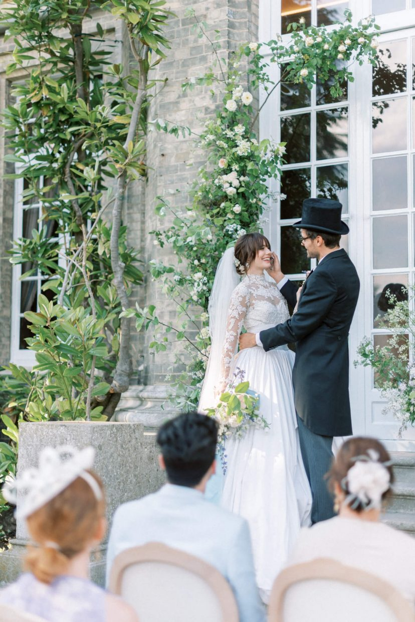 hedsor house spring summer wedding ceremony in the garden; floral installation and flower pillar with david austen roses; bride wearing a marchesa longsleeves white lace wedding gown with silk brocade full ball gown skirt; groom wearing a black top hat with black dior long suit coat and pinstripe trousers | Photo by London and Newcastle UK based light bright and airy Filipina wedding photographer Cristina Ilao