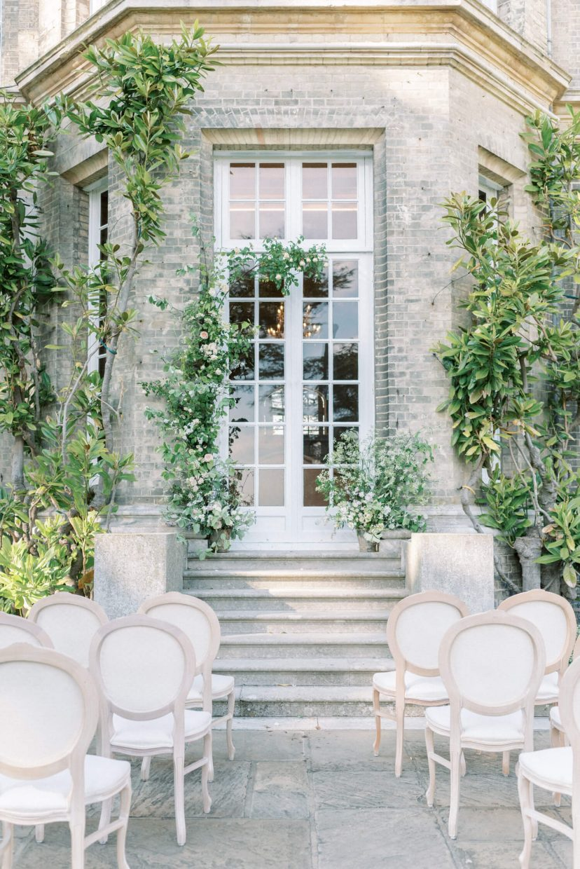 hedsor house spring summer intimate garden wedding ceremony styled set-up with french louis chairs in canvas and wood; flower pillar and floral installation; big double doors an d georgian style architecture backdrop | Photo by London and Newcastle UK based light bright and airy Filipina wedding photographer Cristina Ilao
