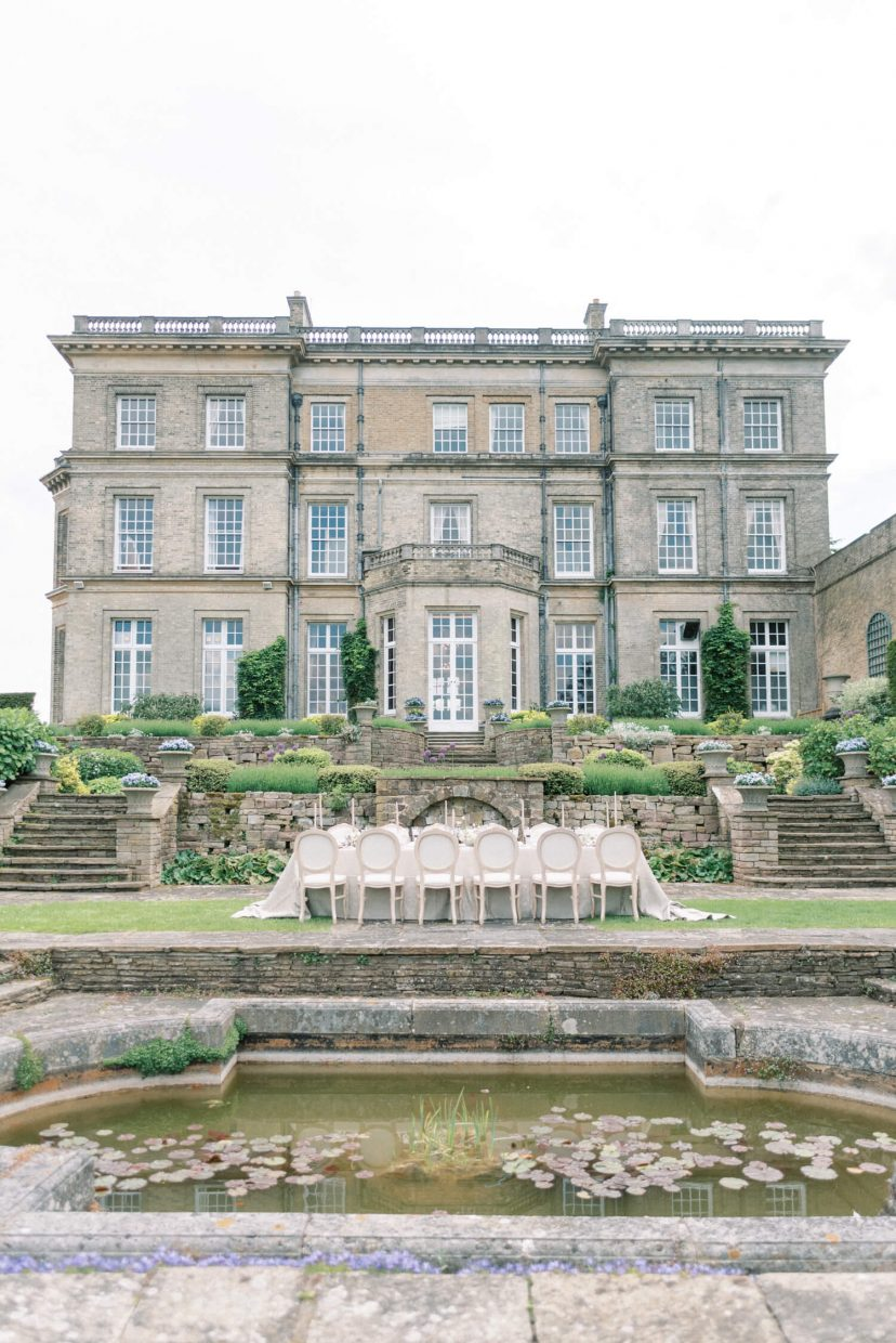 hedsor house spring summer garden intimate wedding reception set-up with long table, french louis chairs; georgian architecture with downton abbey vibes; shooting location for the crown | Photo by London and Newcastle UK based light bright and airy Filipina wedding photographer Cristina Ilao