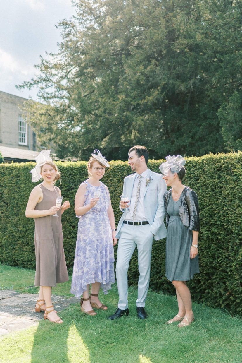 hedsor house spring summer garden wedding guests laughing during the reception; floral summer dress with fascinator | Photo by London and Newcastle UK based light bright and airy Filipina wedding photographer Cristina Ilao
