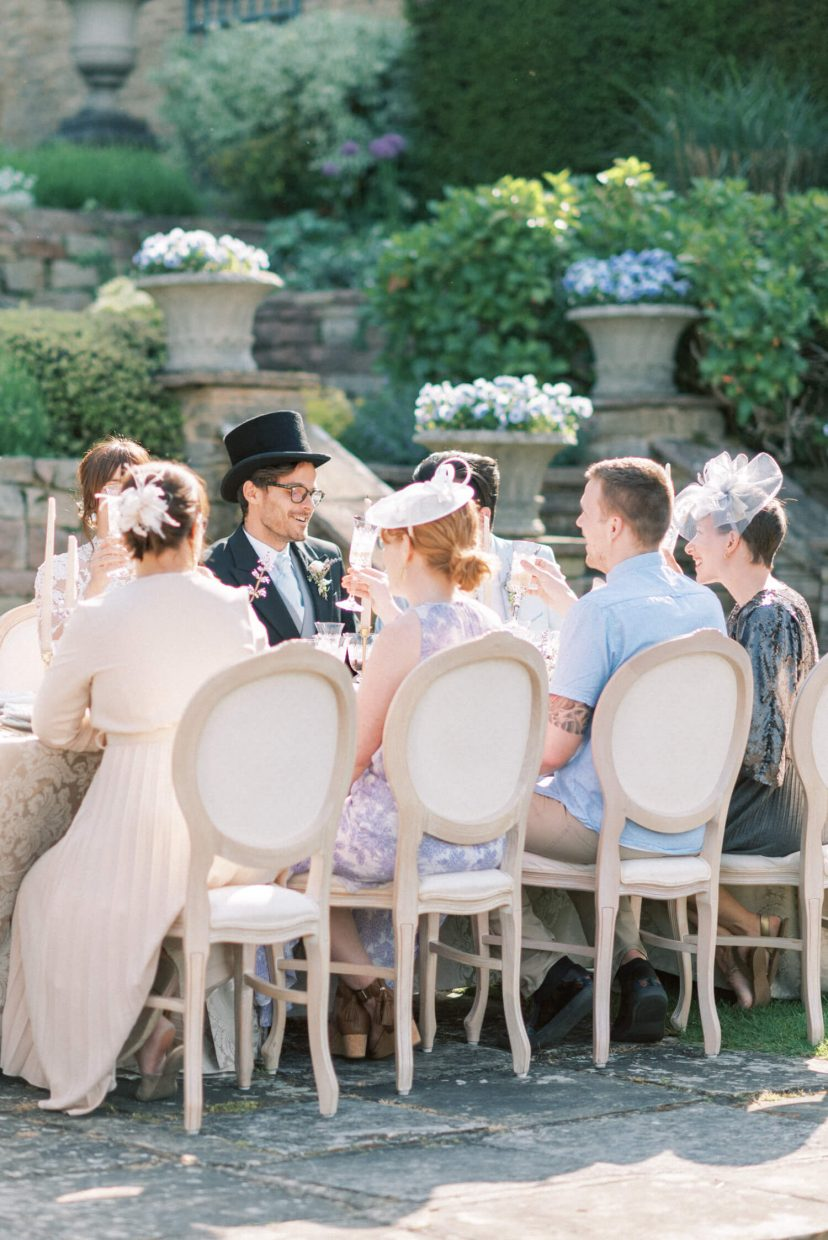 hedsor house spring summer wedding inspiration reception with guests seated at the garden formal english wedding attire with summer dresses and fascinator | Photo by London and Newcastle UK based light bright and airy Filipina wedding photographer Cristina Ilao