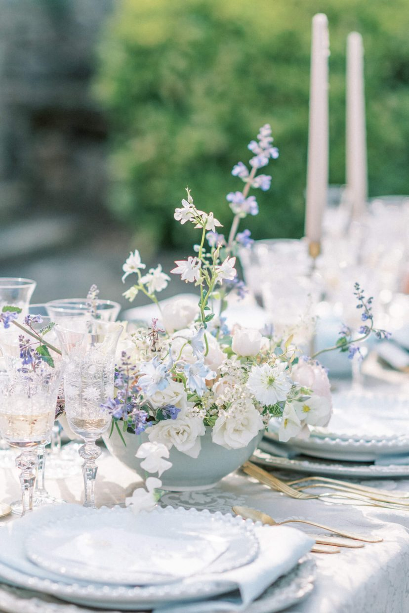 Pastel spring wedding theme; pale blue white and blush pink table flower main central floral arrangement; glass luxury champagne, wine and water goblets glasses; pearl plates | Photo by London and Newcastle UK based light bright and airy Filipina wedding photographer Cristina Ilao