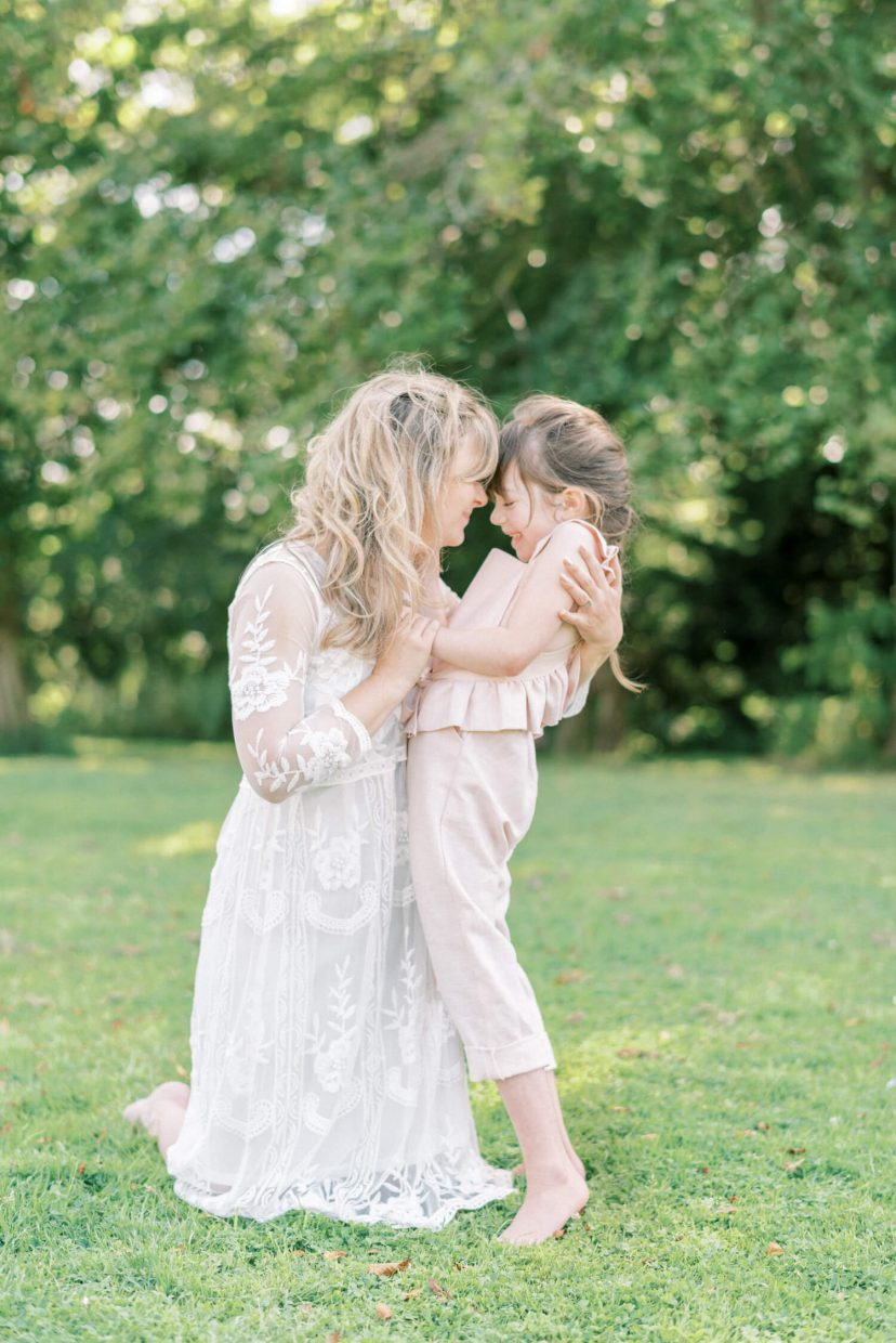 mother and daughter hugging and laughing; lace empire cut lace summer dress; pale blush pink dungaree ruffled and tied in a belt with ribbon | Cottagecore Aesthetic Family photo shoot mini session in Wynyard Hall and Gardens by Cristina Ilao Photography
