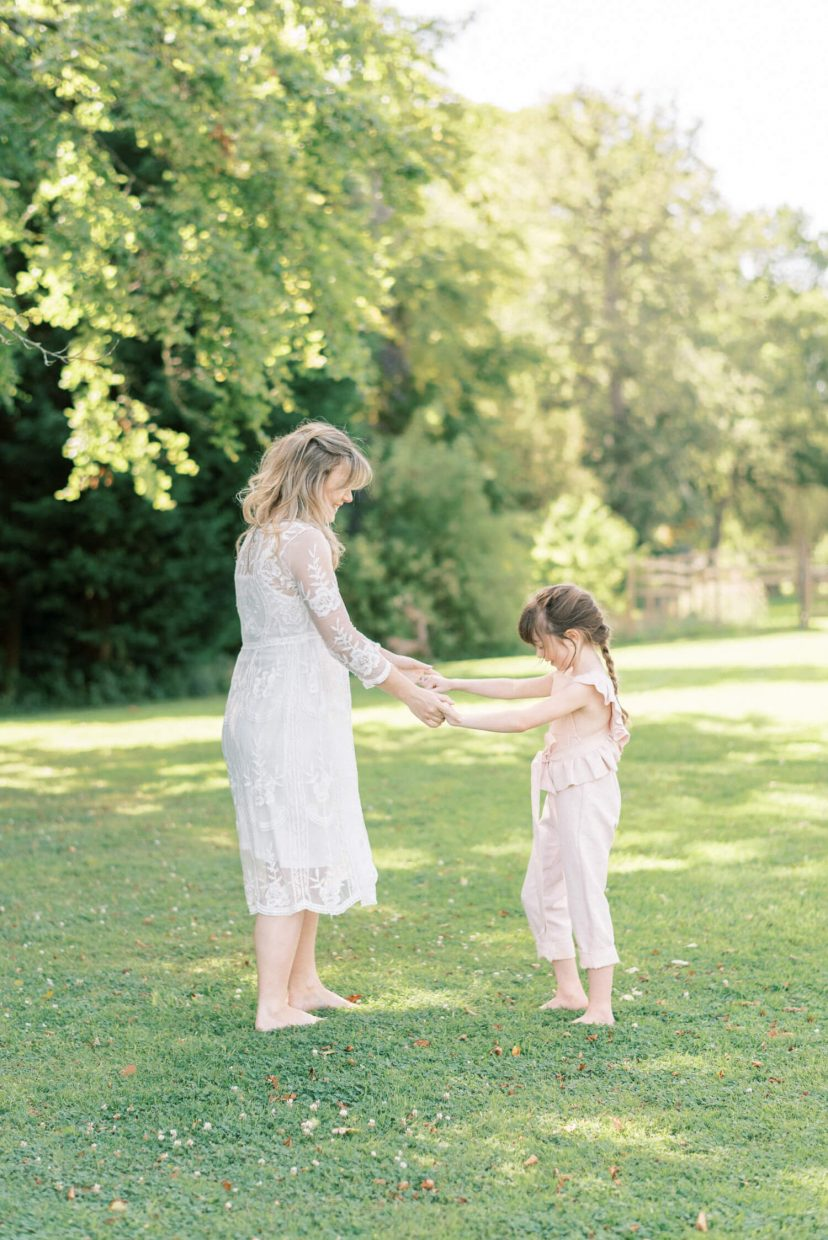 mother and daughter sweet moment dancing and laughing; lace empire cut lace summer dress; pale blush pink dungaree ruffled and tied in a belt with ribbon | Cottagecore Aesthetic Family photo shoot mini session in Wynyard Hall and Gardens by Cristina Ilao Photography