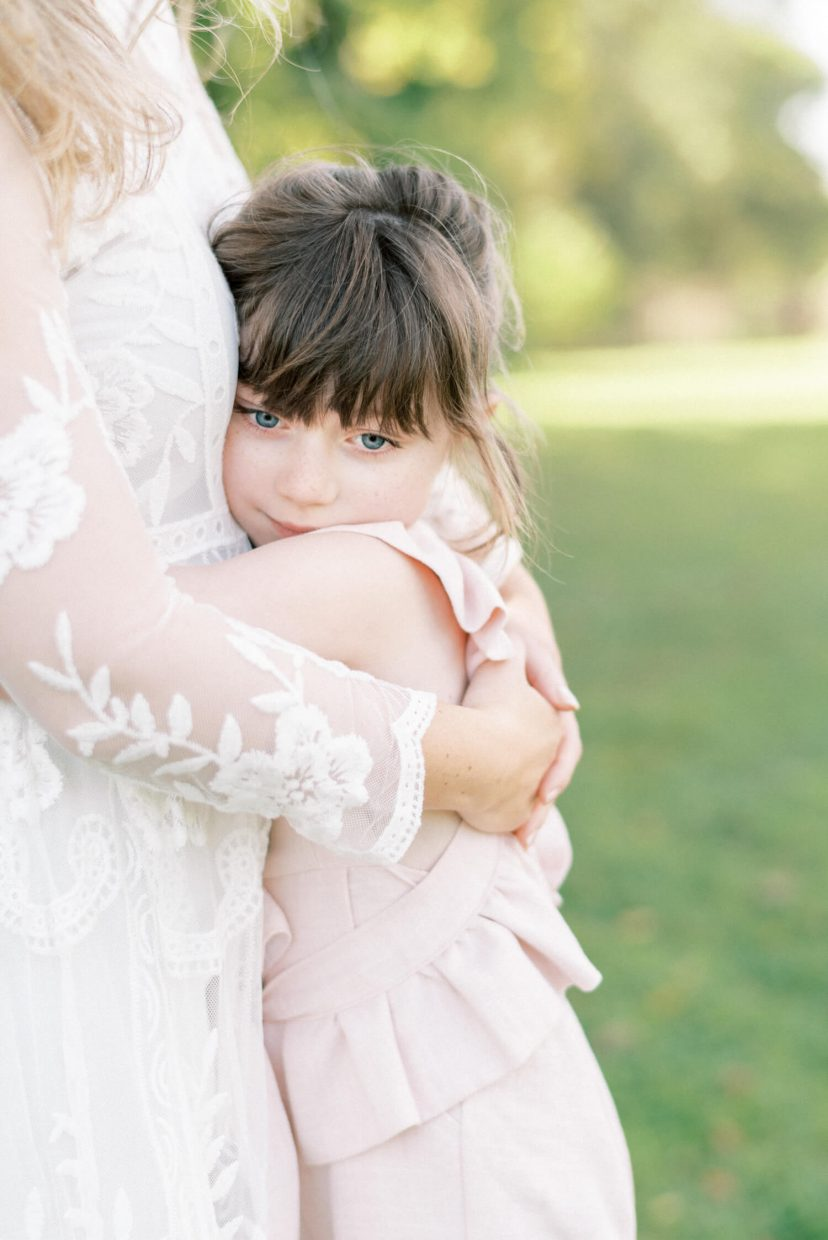 mother and daughter hugging; mother wearing lace empire cut lace summer dress; pale blush pink dungaree ruffled and tied in a belt with ribbon; toddler with bangs fringe and blue eyes, freckles | Cottagecore Aesthetic Family photo shoot mini session in Wynyard Hall and Gardens by Cristina Ilao Photography