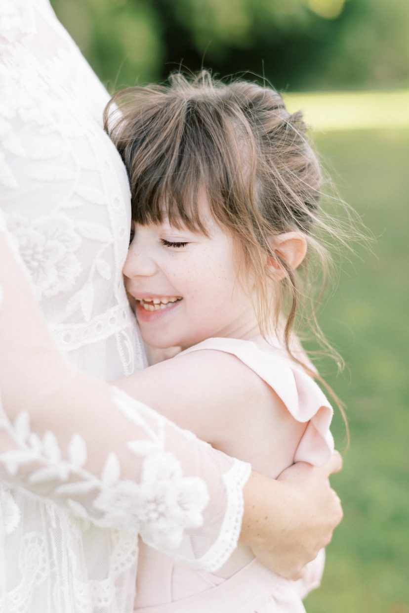 mother and daughter hugging; mother wearing lace empire cut lace summer dress; pale blush pink dungaree ruffled and tied in a belt with ribbon; toddler with bangs fringe and eyes closed while smiling, freckles | Cottagecore Aesthetic Family photo shoot mini session in Wynyard Hall and Gardens by Cristina Ilao Photography