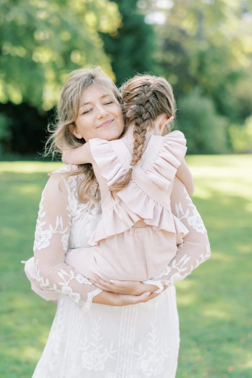 mother and daughter hugging; mother wearing lace empire cut lace summer dress with long sleeves; toddler wearing pale blush pink ruffled dungaree and tied in a belt with ribbon; hair braided in long brown plaits | Cottagecore Aesthetic Family photo shoot mini session in Wynyard Hall and Gardens by Cristina Ilao Photography