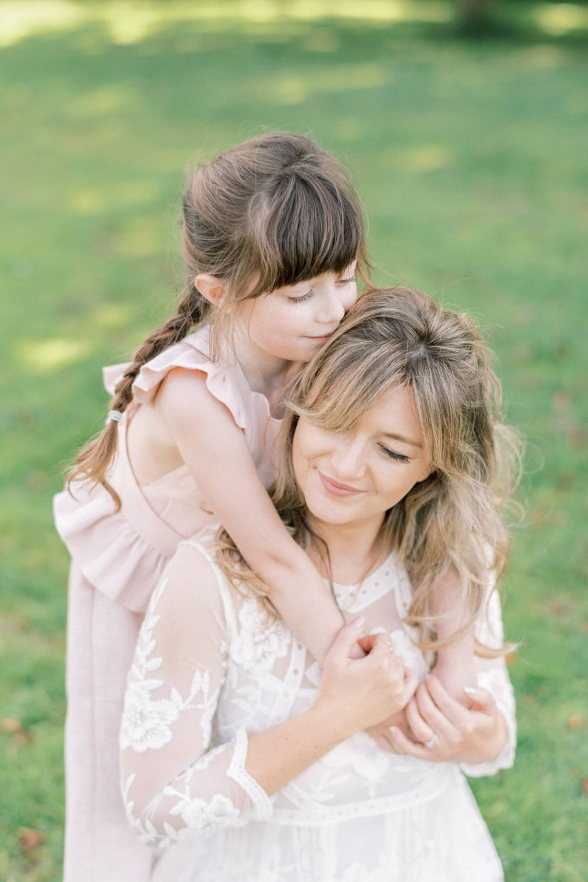 sweet mother and daughter hugging and smiling; mother wearing lace empire cut lace summer dress with long sleeves; toddler wearing pale blush pink ruffled dungaree and tied in a belt with ribbon; hair braided in long brown plaits | Cottagecore Aesthetic Family photo shoot mini session in Wynyard Hall and Gardens by Cristina Ilao Photography