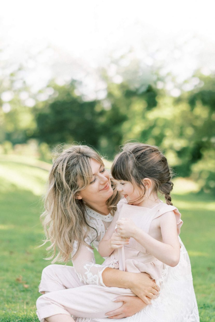 sweet mother and daughter hugging, playing and smiling; mother wearing lace empire cut lace summer dress with long sleeves; blonde hair updo with bangs fringe; toddler wearing pale blush pink ruffled dungaree and tied in a belt with ribbon; hair braided in long brown plaits | Cottagecore Aesthetic Family photo shoot mini session in Wynyard Hall and Gardens by Cristina Ilao Photography