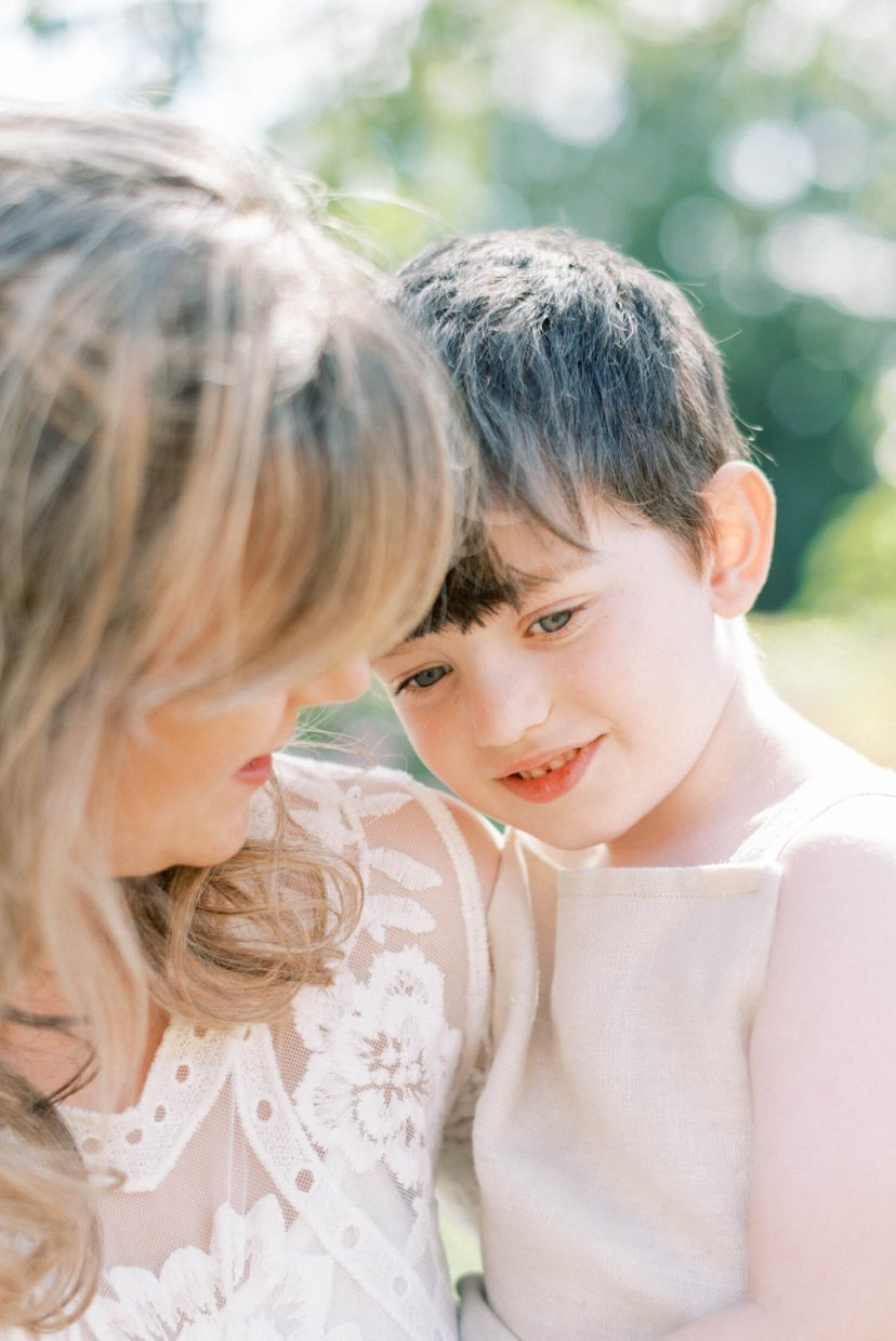sweet mother and son hugging and smiling; mother wearing lace empire cut lace summer dress with long sleeves; blonde hair updo with bangs fringe; toddler son wearing beige neutral dungaree in linen fabric | Cottagecore Aesthetic Family photo shoot mini session in Wynyard Hall and Gardens by Cristina Ilao Photography