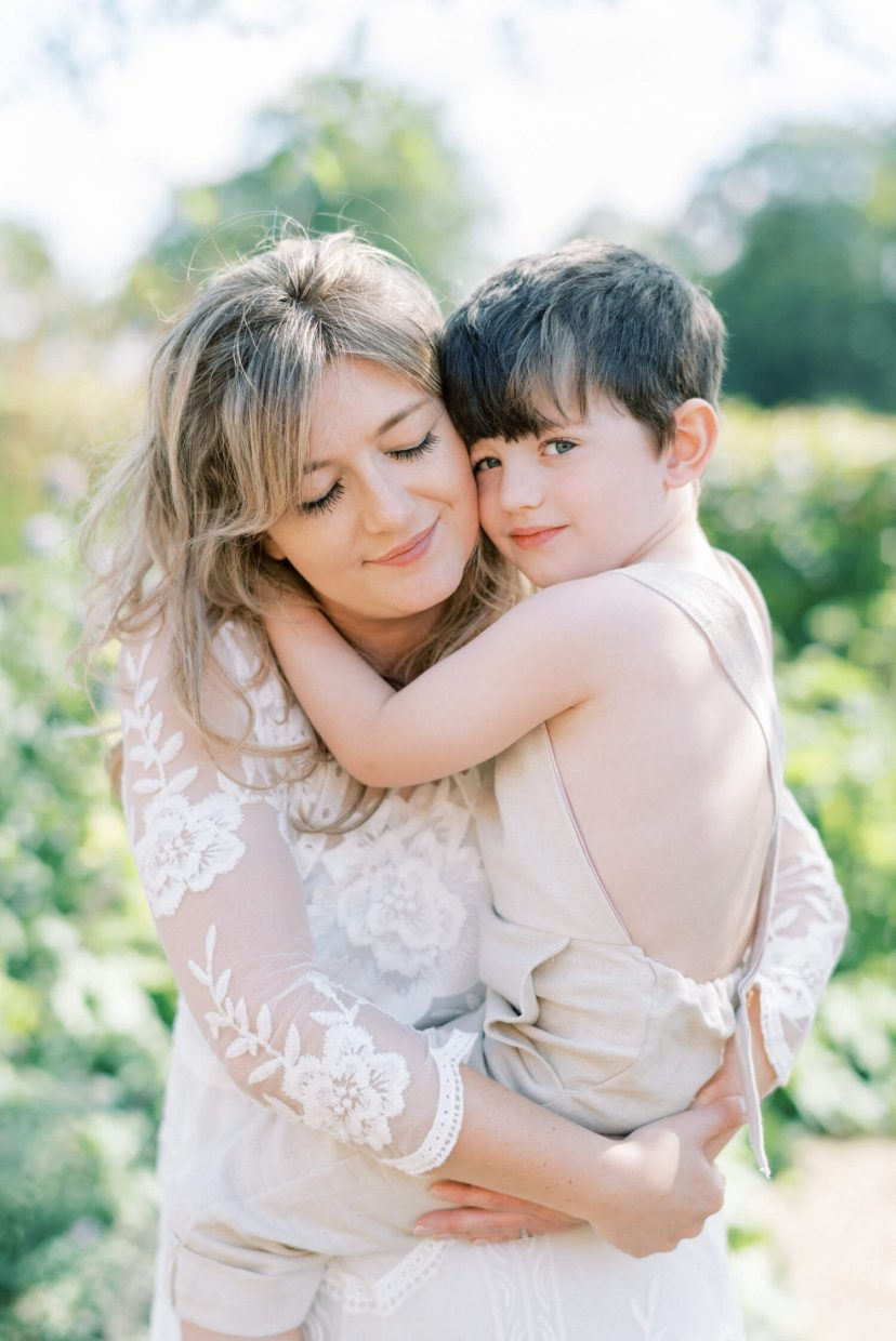 sweet mother and son hugging and smiling; son looking at the camera and mother's eyes are closed while carrying the son; mother wearing lace empire cut lace summer dress with long sleeves; blonde hair updo with bangs fringe; toddler son wearing beige neutral dungaree in linen fabric | Cottagecore Aesthetic Family photo shoot mini session in Wynyard Hall and Gardens by Cristina Ilao Photography
