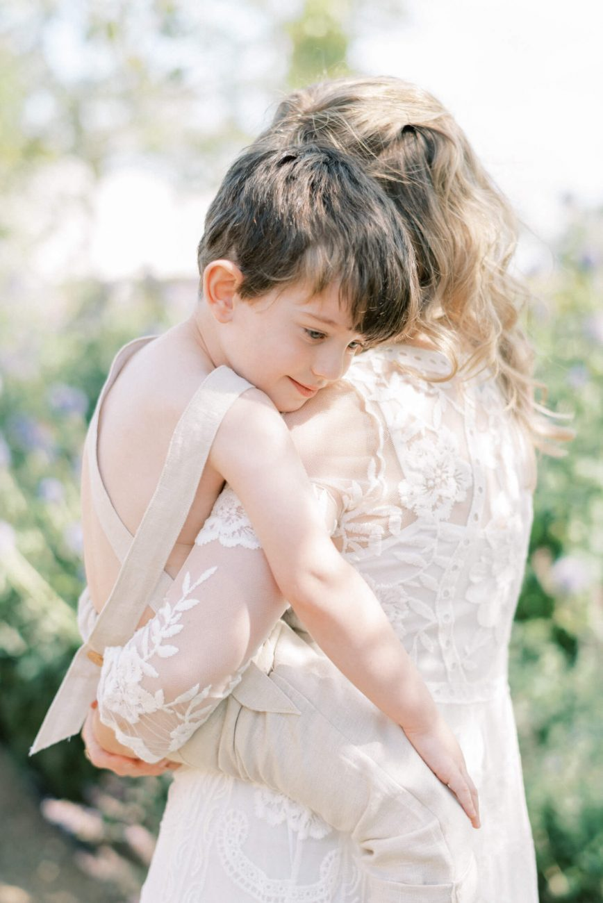 sweet mother and son hugging ; son looking down and mother has back turned while carrying the son; mother wearing lace empire cut lace summer dress with long sleeves; blonde hair updo with bangs fringe; toddler son wearing beige neutral dungaree in linen fabric | Cottagecore Aesthetic Family photo shoot mini session in Wynyard Hall and Gardens by Cristina Ilao Photography