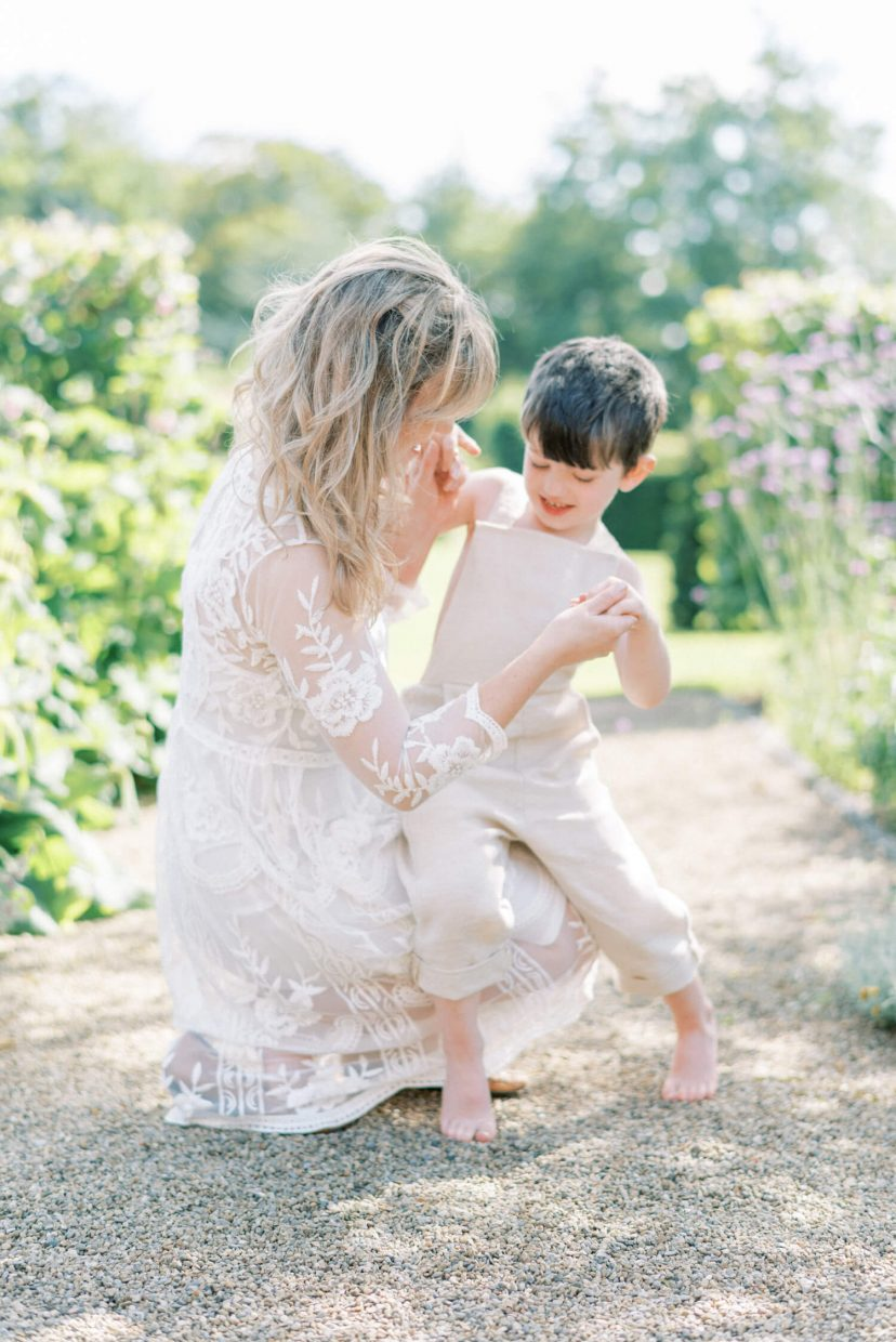 sweet mother and son playing happily ; son looking down and mother is holding the son's hands; mother wearing lace empire cut lace summer dress with long sleeves; blonde hair updo with bangs fringe; toddler son wearing beige neutral dungaree in linen fabric | Cottagecore Aesthetic Family photo shoot mini session in Wynyard Hall and Gardens by Cristina Ilao Photography