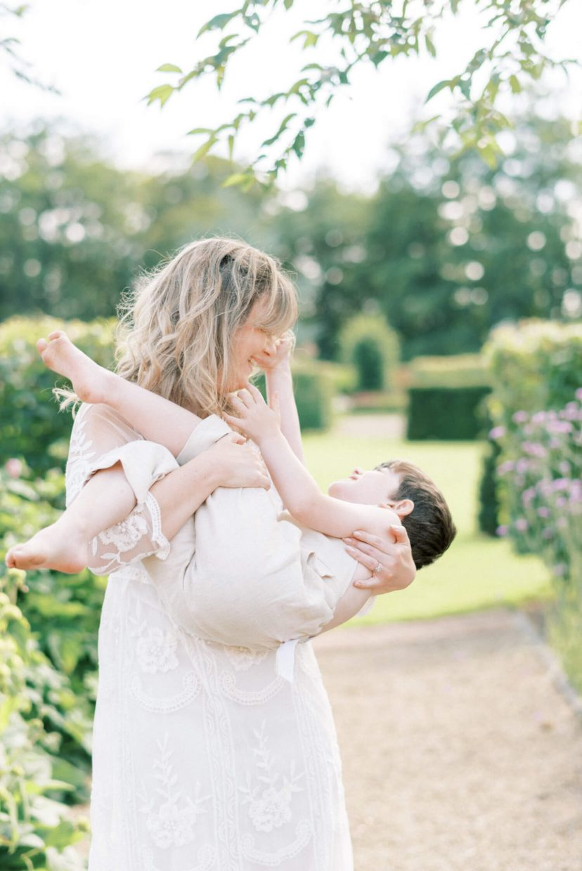 sweet mother and son playing; son laughing and mother is carrying the son; mother wearing lace empire cut lace summer dress with long sleeves; blonde hair updo with bangs fringe; toddler son wearing beige neutral dungaree in linen fabric | Cottagecore Aesthetic Family photo shoot mini session in Wynyard Hall and Gardens by Cristina Ilao Photography
