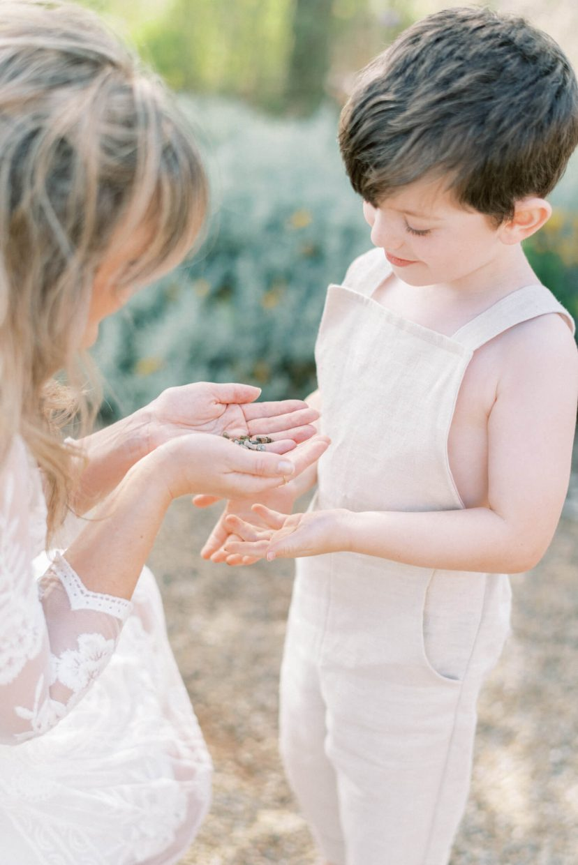 sweet mother and son playing happily ; son looking down and mother is putting stones on son's hands; mother wearing lace empire cut lace summer dress with long sleeves; blonde hair updo with bangs fringe; toddler son wearing beige neutral dungaree in linen fabric | Cottagecore Aesthetic Family photo shoot mini session in Wynyard Hall and Gardens by Cristina Ilao Photography