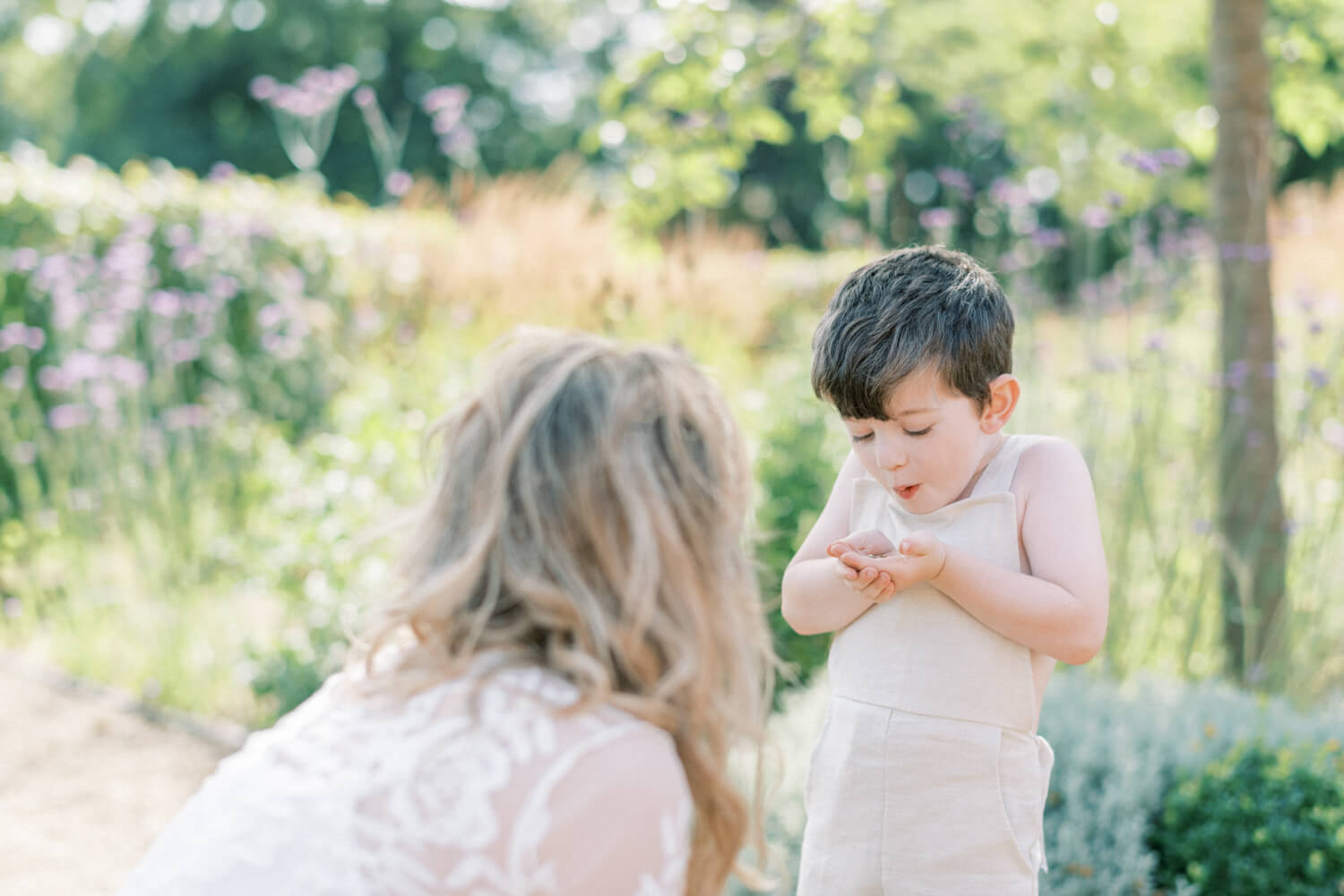 sweet mother and son playing happily ; son is blowing on his hands while mother is looking; mother wearing lace empire cut lace summer dress with long sleeves; blonde hair updo with bangs fringe; toddler son wearing beige neutral dungaree in linen fabric | Cottagecore Aesthetic Family photo shoot mini session in Wynyard Hall and Gardens by Cristina Ilao Photography