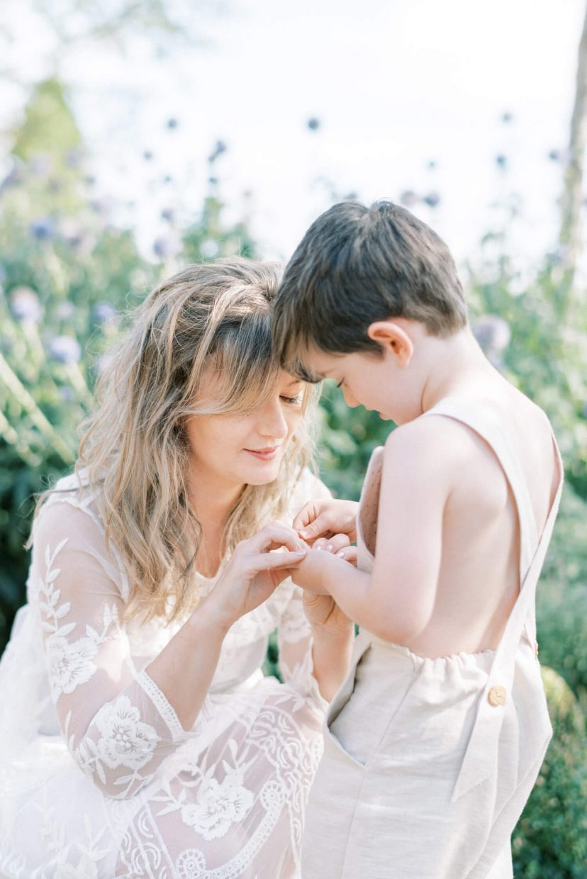 sweet mother and son playing happily ; son looking down and mother is holding her son's hands; mother wearing lace empire cut lace summer dress with long sleeves; blonde hair updo with bangs fringe; toddler son wearing beige neutral dungaree in linen fabric | Cottagecore Aesthetic Family photo shoot mini session in Wynyard Hall and Gardens by Cristina Ilao Photography