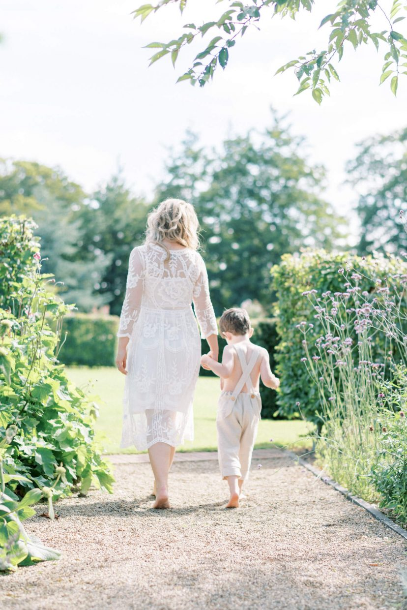sweet mother and son walking barefoot ; son looking down and mother is holding her son's hand; mother wearing lace empire cut lace summer dress with long sleeves; blonde hair updo with bangs fringe; toddler son wearing beige neutral dungaree in linen fabric | Cottagecore Aesthetic Family photo shoot mini session in Wynyard Hall and Gardens by Cristina Ilao Photography