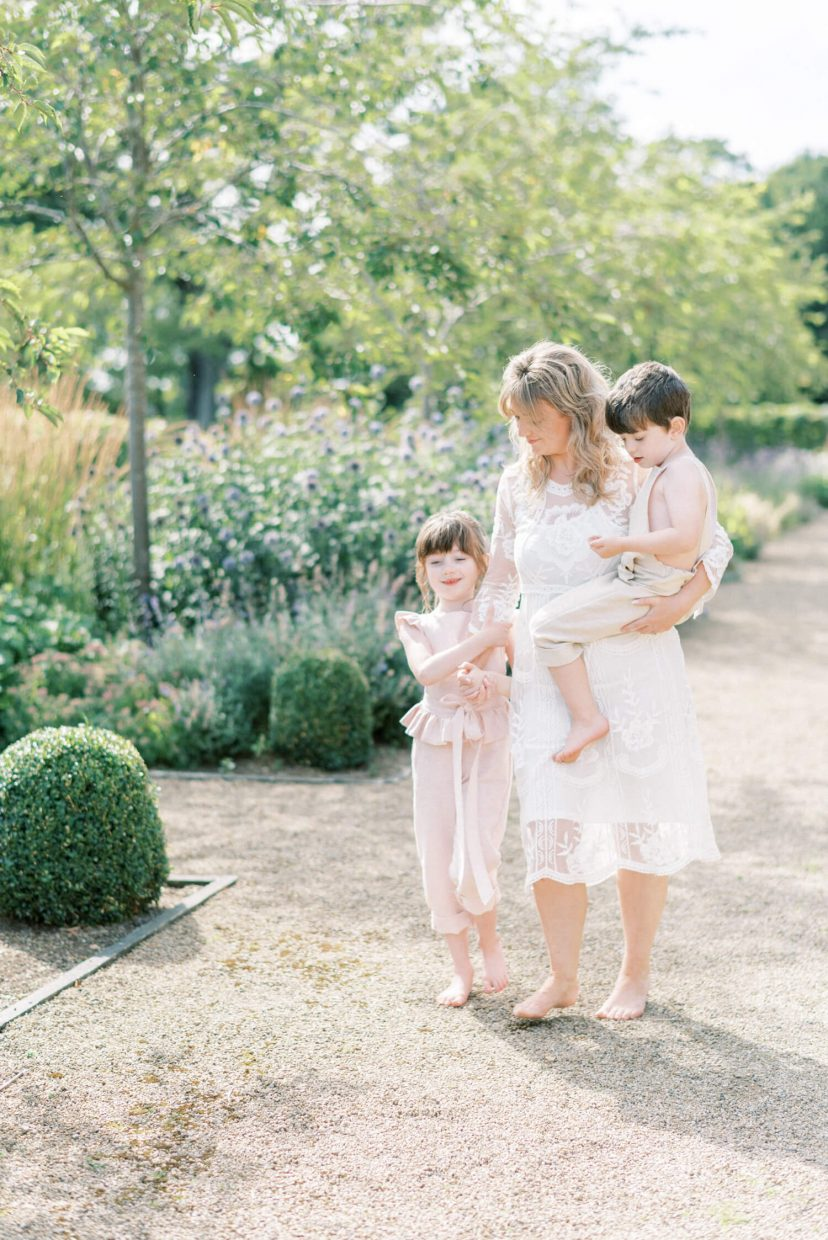 sweet mother daughter and toddler son walking barefoot ; daughter looking down and mother is carrying the son; mother is wearing lace empire cut lace summer dress with long sleeves; blonde hair updo with bangs fringe; toddler son wearing beige neutral dungaree in linen fabric; daughter is wearing a pale blush pink dungaree ruffled with ribbon linen | Cottagecore Aesthetic Family photo shoot mini session in Wynyard Hall and Gardens by Cristina Ilao Photography