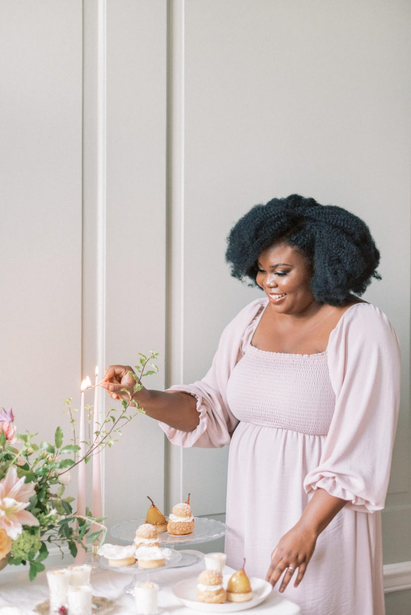 half body shot of a black woman lighting a nude blush pink ester & erik taper candle, showing luxury wedding desserts on a crystal serving dish, wearing a pale blush pink flowy empire cut dress with large puffy sleeves, natural fresh no make-up make-up look, loose hairstyle and smiling down on the desserts. Photo is from a personal branding shoot at Thorpe Manor by London based UK light and airy fine art Filipina wedding photographer.