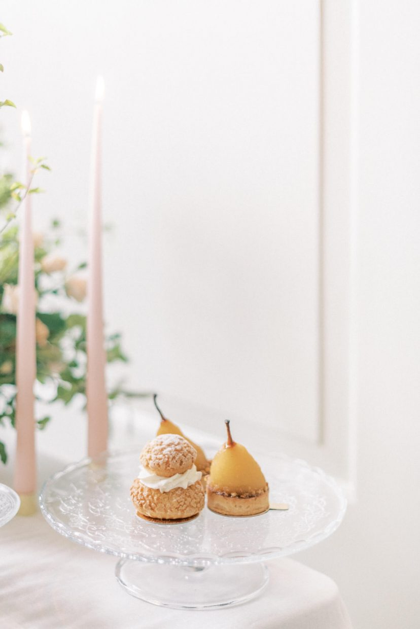 close-up shot of luxury wedding desserts pear and Croquembouche on a crystal serving dish, nude pale blush pink taper candles on brass simple candle stick holders, white linen table cloth and white wall with wooden paneling. Photo is from a personal branding shoot at Thorpe Manor by London based UK light and airy fine art Filipina wedding photographer.