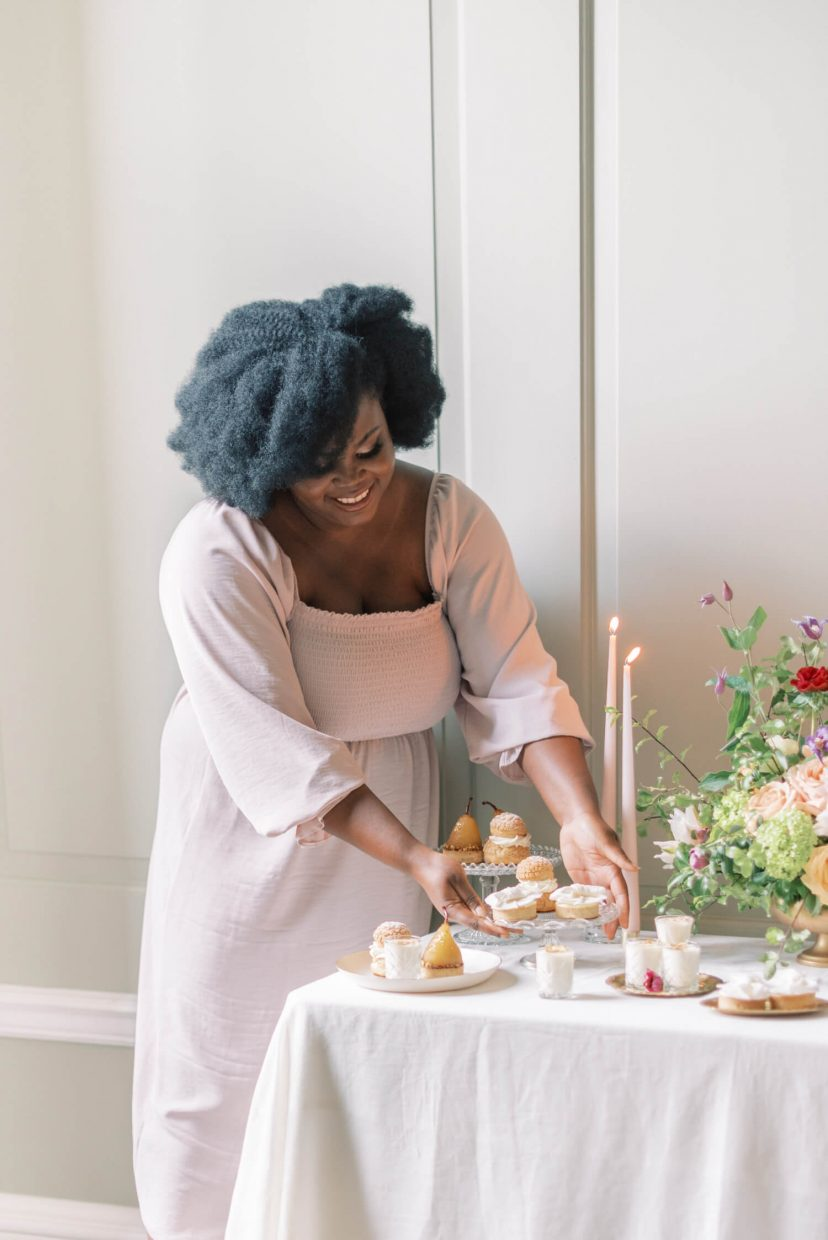 half body shot of a black woman standing by a luxury wedding dessert table with a floral centrepiece, wearing a pale blush pink flowy empire cut dress with large puffy sleeves, natural fresh no make-up make-up look, loose hairstyle and smiling down while fixing the desserts. Photo is from a personal branding shoot at Thorpe Manor by London based UK light and airy fine art Filipina wedding photographer.