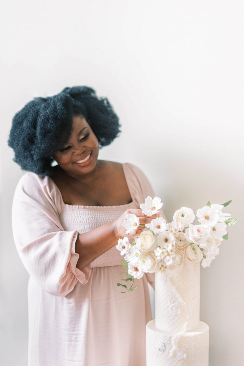 half body shot of a black woman standing by a multiple tier luxury white wedding cake with sugar flowers, wearing a pale blush pink flowy empire cut dress with large puffy sleeves, natural fresh no make-up make-up look, loose hairstyle and smiling down while fixing the sugar flowers. Photo is from a personal branding shoot at Thorpe Manor by London based UK light and airy fine art Filipina wedding photographer.