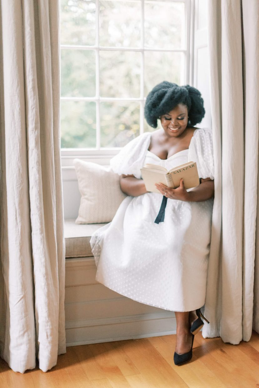 full body shot of a black woman sitting by a large victorian style window with legs elegantly crossed like royalties, wearing a white flowy polka dot dress with a black belt and large puffy sleeves, natural fresh no make-up make-up look, loose hairstyle and smiling at the camera while reading a vintage book with a white linen cover. Photo is from a personal branding shoot at Thorpe Manor by London based UK light and airy fine art Filipina wedding photographer.