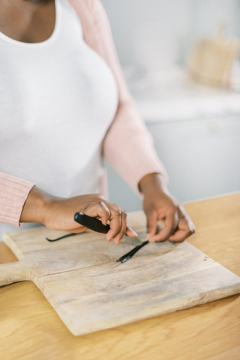 close-up of hands peeling and removing the seeds from a vanilla pod using a knife with a black handle. In photo: black woman wearing a white shirt with blush pink cardigan, light wooden chopping board and oak wood kitchen table countertop, white background. Photo is from a personal branding shoot at Thorpe Manor by London based UK light and airy fine art Filipina wedding photographer.