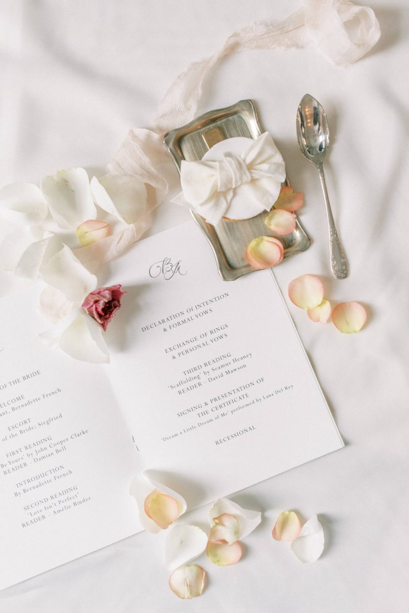 flatlay of wedding invitation, blush pale pink crumpled silk ribbons, silver antique vintage dessert spoon and serving tray, side tray, rose petals in peach and white, luxury dessert with ribbon detail on plain white fabric background | Photo by Cristina Ilao Photography. More at www.cristinailao.com