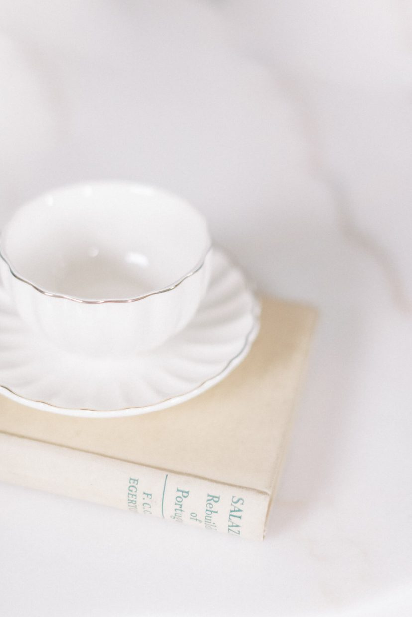 white fine bone china tea cup and saucer on top of beige vintage antique book and plain white tabletop | Photo by Cristina Ilao Photography. More at www.cristinailao.com