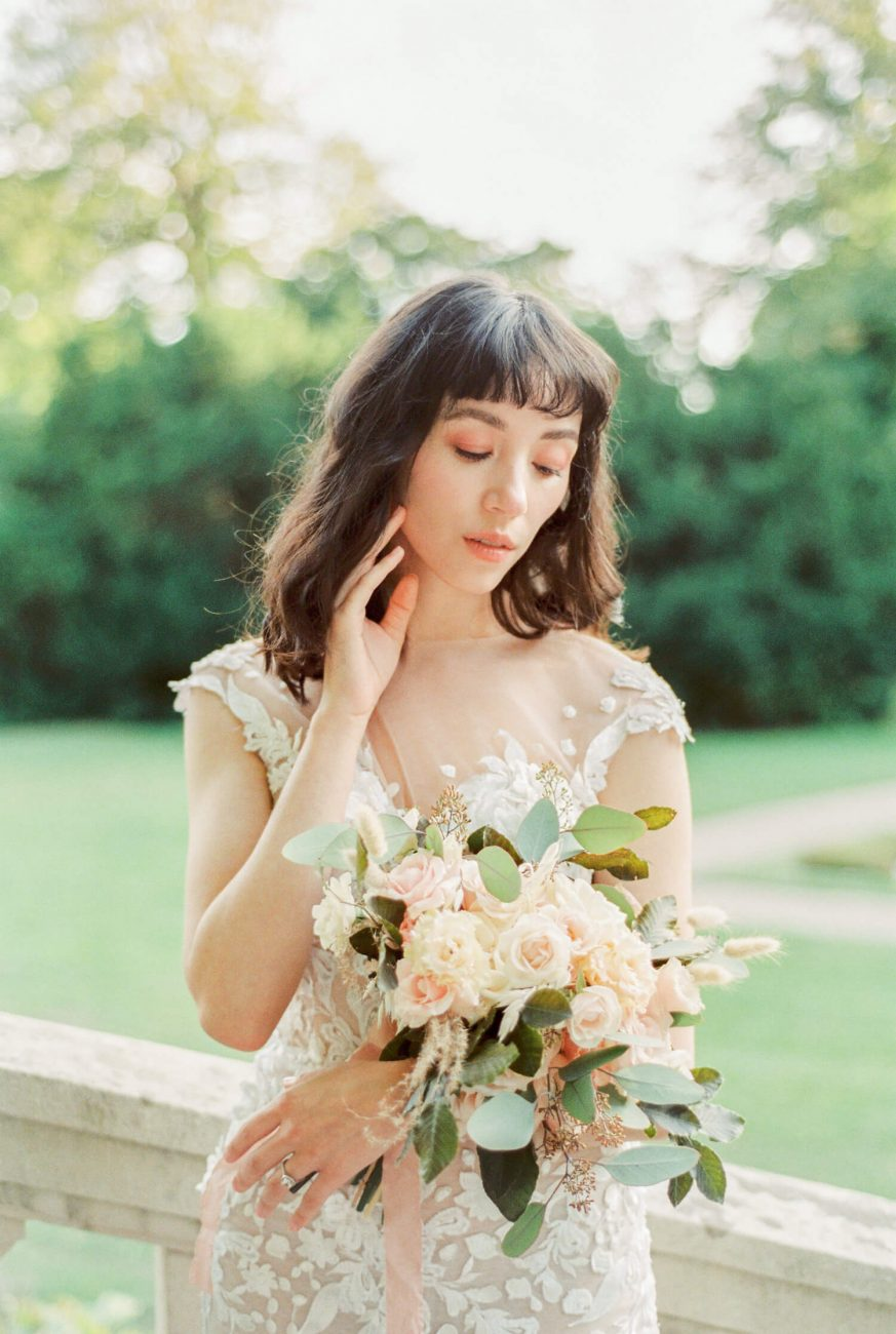 Close up portrait of asian japanese bride with natural neutral classic bridal make-up and curled short loose hair with bangs fringe | Shot on Film using Nikon F 100 and Fujifilm Pro 400 by UK light and airy wedding photographer Cristina Ilao