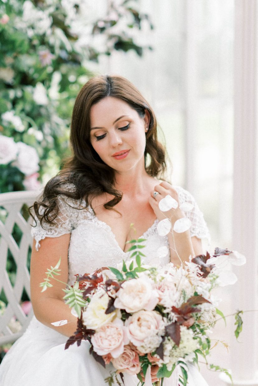bride with natural neutral palette make-up and loose natural curle styled bridal hair holding a spring summer wedding bouquet with large david austin pale peach pink and white roses and honesty sprigs - Venue: Wollaton Hall Camellia House (cast iron glass house) in Nottinghamshire. Photo by London and Newcastle UK based Filipina fine art light bright and airy wedding and portrait photographer Cristina Ilao, more at www.cristinailao.com