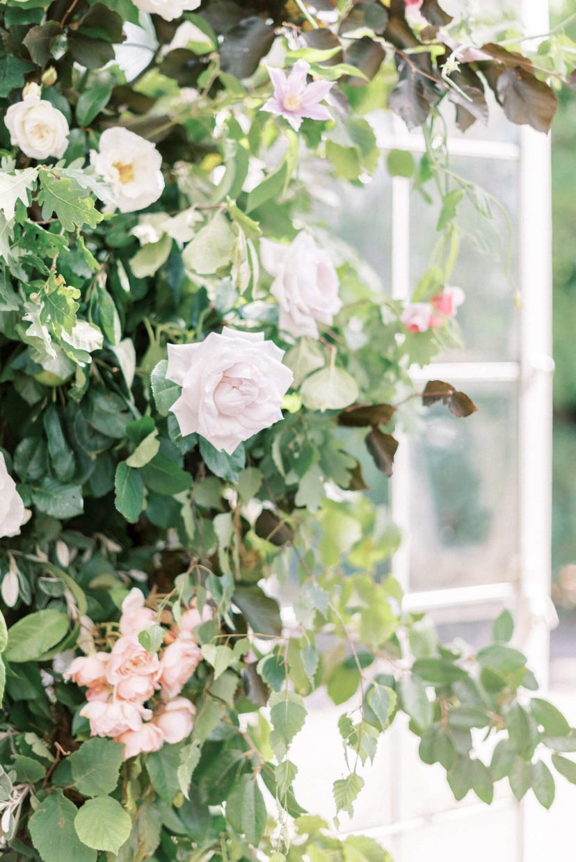 large david austin roses and foliage on a flower pillar close-up image showing light bright airy wedding photography inside the glass house - Venue: Wollaton Hall Camellia House (cast iron glass house) in Nottinghamshire. Photo by London and Newcastle UK based Filipina fine art light bright and airy wedding and portrait photographer Cristina Ilao, more at www.cristinailao.com